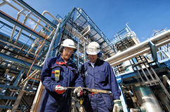 Oil, gas, pipelines and workers. Oil and gas workers in front of large refinery, petrochemical industries stock images