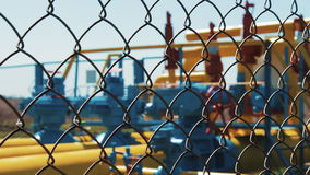 Oil and gas plant. Pumping station behind the fence in the defocus. Fence mesh. Check valves on the pipeline. Oil stock video