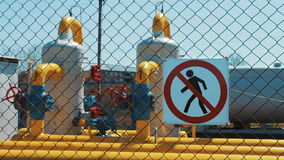 Oil and gas plant. Sign for unauthorized entry is prohibited. Gas pipeline with a manometer and a valve. The territory. Behind the fence from the grid. Gas stock footage