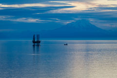 Oil and gas platform in the Cook Inlet. Oil and gas platform reflecting on water in the Cook Inlet with snow capped mountains in the background Stock Photos