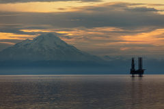 Oil and gas platform in Cook Inlet with snowcapped mountain Royalty Free Stock Photo