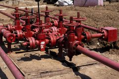 Oil and gas processing plant with pipe line valves. Oil pipeline valves in the oil and gas industry. Valve plug an oil pipeline in. The field on a sunny summer royalty free stock images