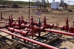 Oil and gas processing plant with pipe line valves. Oil pipeline valves in the oil and gas industry. Valve plug an oil pipeline in. The field on a sunny summer royalty free stock photography