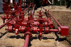 Oil and gas processing plant with pipe line valves. Oil pipeline valves in the oil and gas industry. Valve plug an oil pipeline in. The field on a sunny summer royalty free stock image