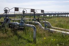 Oil and gas processing plant with pipe line valves. Oil pipeline valves in the oil and gas industry. Valve plug an oil pipeline in. The field on a sunny summer stock image