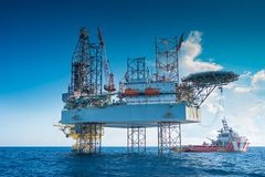 Offshore oil and gas jackup drilling rig work over remote wellhead platform to completion oil and gas produce well . Oil and gas production and exploration, oil royalty free stock photography