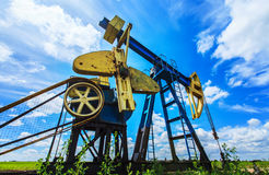 Oil and gas pump operating. Oil and gas pump machinery profiled on blue sky Stock Photography