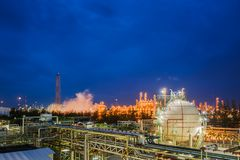 Oil and gas refinery. Gas storage sphere tanks and pipeline in oil and gas refinery industrial plant with glitter lighting industry estate at twilight royalty free stock images