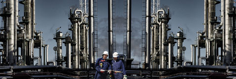 Oil and gas refinery with workers in foreground. Giant oil, gas and fuel industry, refinery with two oil workers in foreground, panoramic view Stock Photography