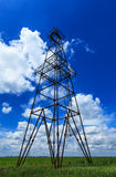 Oil and gas rig profiled on blue sky with clouds Stock Photography
