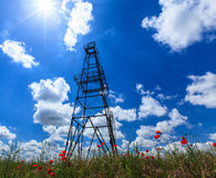 Oil and gas rig profiled on blue sky with clouds Stock Photos