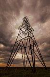 Oil and gas rig profiled on ominous stormy sky stock image