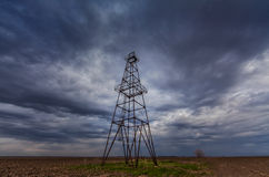 Oil and gas rig profiled on ominous stormy sky royalty free stock image
