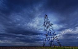 Oil and gas rig profiled on ominous stormy sky Royalty Free Stock Images