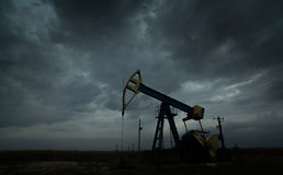 Oil and gas rig profiled on storm clouds Royalty Free Stock Photos