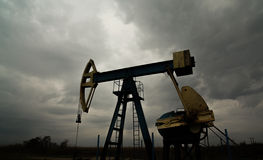 Oil and gas rig profiled on storm clouds Stock Images