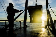 Oil and gas. Silhouette of worker recovering robotics Remote Operated Vehicle ROV after entering sea surface during oil and gas pipeline inspection in the middle stock photo