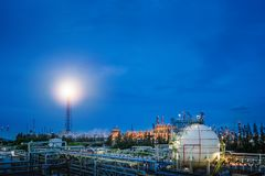 Oil and gas storage. Gas storage sphere tanks and pipeline in oil and gas refinery industrial plant with flare stack on blue sky twilight background royalty free stock photography