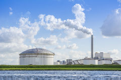 Oil and gas storage tanks placed allong the shore. Stock Image