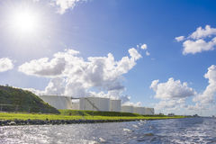 Oil and gas storage tanks placed allong the shore. Royalty Free Stock Photos