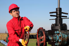 Satisfied Worker Holding Money At Oil Field Stock Image