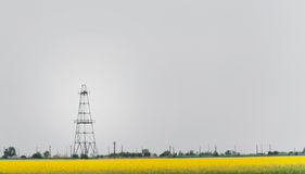 Oil and gas well rig, outlined rural canola field. Oil and gas well rig , outlined on rural canola field, on an overcast day Royalty Free Stock Photos