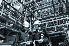 Oil and gas workers inside industry. Two oil and gas workers, engineers, inside giant refinery construction stock images