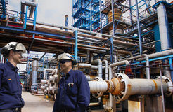 Oil and gas workers inside large refinery industry. Two engineers, oil and gas workers inside refinery industry, main fuelpipelines showing in background Stock Photography
