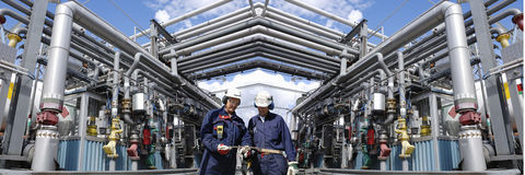 Oil and gas workers inside refinery royalty free stock image