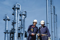 Oil and gas workers inside refinery. Two oil and gas workers with large refinery in background Royalty Free Stock Photography