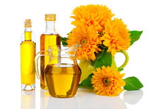 Oil in glass bottle and jug with sunflowers Stock Photography
