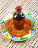 Oil and grinded turmeric. On wooden mat Royalty Free Stock Photo