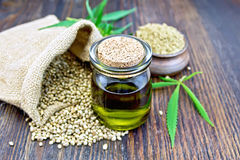 Oil hemp with flour on board. Hemp oil in a glass jar with flour in a clay bowl and grain in a bag, cannabis leaves and stalks on a wooden boards background stock photo