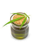 Oil hemp in glass jar with leaf on lid. Hemp oil in a glass jar with a sheet on a lid with a light shade on white background stock photo