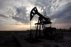 Oil horse head pump in the field. Oil horse head pump on field in sunset Stock Photos