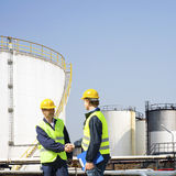 Oil industry. Two oil industry workers shaking hands in front of the storage tanks of a petrochemical refinary Royalty Free Stock Image