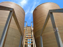 Oil industry tanks. Symmetrical oil industry tanks with ladder and sky Stock Image