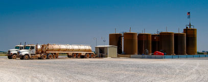 Oil industry trucks unloading. Two oil industry trucks unloading at an oil industry tank facility with an American flag flying Royalty Free Stock Photo