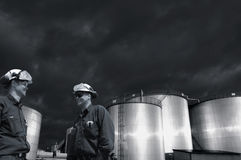 Oil industry, workers and dark stormy clouds Stock Images