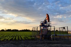 Pumpjack and agricultural field during twilight time. Oil jack in an east European oil field situated in the middle of a farmland - dirty technology Stock Photos