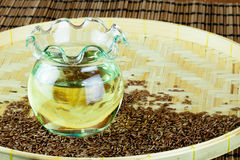 Oil in jar extracted from flax seeds with the sees on flat woven basket. Stock Photography