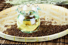 Oil in jar extracted from flax seeds with the sees on flat woven basket. Royalty Free Stock Image