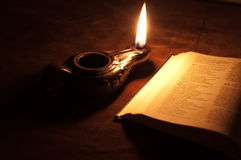 Oil lamp and Bible. Oil lamp and open Bible shot at a single flame light Royalty Free Stock Photography