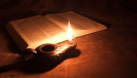 Oil lamp and Bible. Oil lamp and open Bible shot at a single flame light royalty free stock images