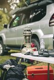 Oil lamp and binoculars over camping table. In the forest with  offroad vehicle in the background Stock Images