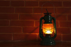 Oil lamp. An oil lamp lantern style lighting in front of a brickwall background Royalty Free Stock Photo