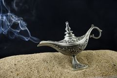 Fairy-tale oil lamp Aladin smokes. The oil lamp lies in the sand and smokes Royalty Free Stock Photos