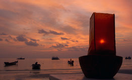 Oil lamp sunset. An oil lamp burning by the beach at sunset Stock Images