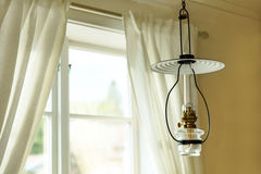 Oil lamp and a window. With white curtains during a day Stock Image