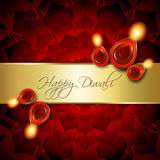 Oil lamps with diwali greetings over red background. Oil lamps with diwali greetings over dark red background Royalty Free Stock Photo